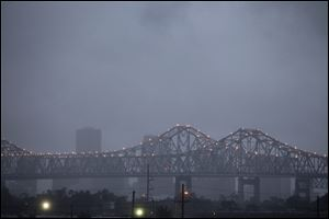 Heavy rain clouds from approaching Tropical Storm Lee form over the skyline of New Orleans and the Crescent City Connection bridges at dusk Friday.
