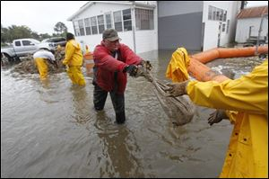 Workers hand off sandbags to to to stop flooding waters from Bayou Barataria encroaching on homes and businesses in the aftermath of Tropical Storm Lee in the town of Jean Lafitte, La., just outside New Orleans on Saturday.