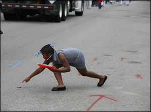 Constance Davis-Bruster, 8, of West Toledo, stretches to grab a piece of candy during the parade.