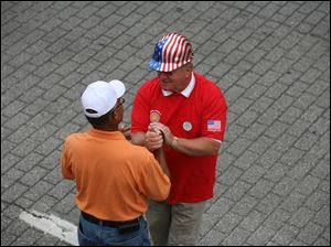 Dennis Duffey, of the International Brotherhood of Electrical Workers Local 8, right, greets Frank Badgett of West Toledo.