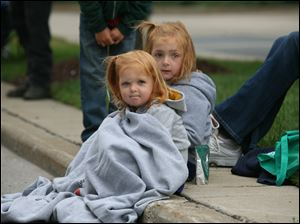 Kate Hildebrand, 6, right, and her sister Colleen Hildebrand, both of Waterville, huddle under a blanket as they watch the parade downtown.