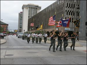 Officers of the Lucas County Sheriff's Department march down the street carrying the American, Ohio, Lucas County, and sheriff's department flags.
