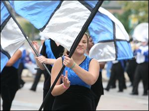 A colorguard member spins her flag in the chilly September air during the parade.