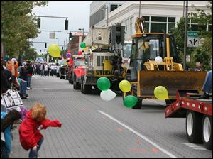 Trucks and other construction equipment is displayed as part of the Labor Day parade in Toledo.