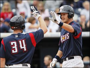 Toledo Mud Hens first baseman Ryan Strieby, right, is congratulated by teammate Clete Thomas left, after his home run in the eighth inning of their game against the Columbus Clippers at Fifth Third Field in Toledo, Monday, September 5, 2011.  The Mud Hens beat the Clippers 3-1 in the final game of the season.