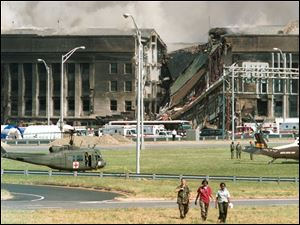 Three rescue workers walk away from the crash site at the Pentagon in Arlington, Va., in this Sept. 11, 2001, file photo.