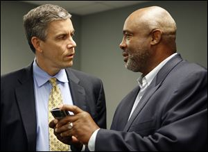 U.S. Secretary of Education Arne Duncan, left, talks with Toledo Board of Education member Larry Sykes during Mr. Duncan's visit to the Toledo Federation of Teachers headquarters.