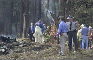 Firefighters and emergency personnel investigate the fatal crash scene of Flight 93 in Shanksville, Pa.