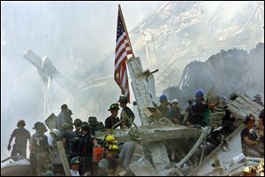 An American flag flies over the rubble of the collapsed World Trade Center buildings in New York in this Sept. 13, 2001, file photo.