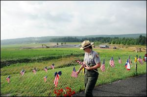 Park Ranger Wendy Clay removes items from the Flight 93 temporary memorial to be archived earlier this summer. There will be 40 trees in the memorial grove of the yet-to-be-completed Flight 93 National Memorial near Shanksville, Pa. The trees represent each of the passengers and crew members who died.