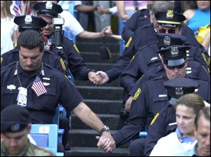 Members of the New York Police Department pray as they hold hands across the aisle at Yankee Stadium on Sept. 23, 2001, at the interfaith  memorial service in honor of the victims of the Sept. 11th attack on the World Trade Center.