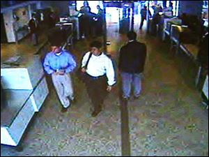 This image made from surveillance video from Washington's Dulles Airport shows two of the five hijackers on the morning of Sept. 11, 2001, man in blue shirt, left, and white shirt, second from left, leaving a security checkpoint before boarding American Airlines flight 77 that later crashed into the Pentagon.