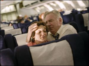 "Becky London and Tom O'Rourke as Jean and Donald Peterson comfort one another aboard United Airlines Flight 93 in the unflinching drama ""United 93."""