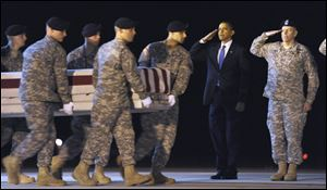 President Barack Obama salutes with Maj. Gen. Daniel Wright, right, as a carry team carries the transfer case containing the remains of Army Sgt. Dale R. Griffin of Terre Haute, Ind., who died in Afghanistan, during a dignified transfer at Dover Air Force Base in Dover, Del., on Oct. 29, 2009.