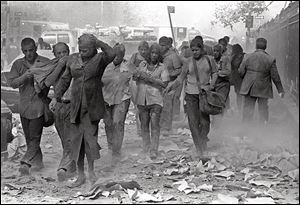 People covered in dust walk over debris near the World Trade Center in New York in this Sept. 11, 2001, file photo.