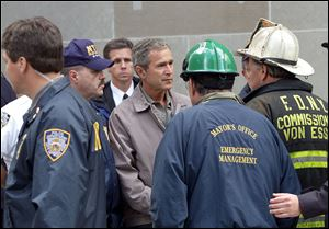 Then President George W. Bush, center, talks to former New York City Fire Commissioner Thomas Van Essen, right, wearing helmet, as New York Police Commissioner Bernard Kerik, left, and former New York City Mayor Rudolph Giuliani, foreground with back to camera, look on during a Sept. 14, 2001, tour of the World Trade Center in New York.
