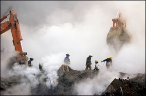 Firefighters make their way over the ruins of the World Trade Center through clouds of smoke at ground zero in New York, in this Oct. 11, 2001 file photo.