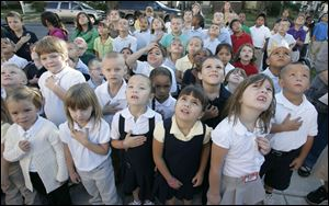 Students at Navarre Elementary School in East Toledo watch as the U.S. flag is raised in front of their school during a 2010 ceremony to remember the terrorist attacks of September 11, 2001.