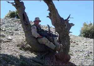 Pat Tillman rests on a tree in Afghanistan.