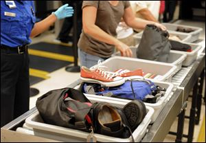 Airline passengers retrieve their scanned belongings while going through the Transportation Security Administration security checkpoint at Hartsfield-Jackson Atlanta International Airport in Atlanta.