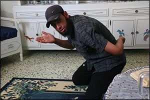 Tunisian Islamist Saber Ragoubi, 28, shows how he was forced to kneel when he first arrived at Morneguia prison and had his teeth kicked out during an interview at his home in Sousse, Tunisia. Tunisia passed anti-terror laws in 2003 and the staunchly secular regime used them to crack down on signs of piety, to protect itself and to prevent the rise of Islamic militancy. It convicted 62 people under the laws in 2006, 308 in 2007 and 633 in 2009, according to the U.N. One of those convicted was Ragoubi.