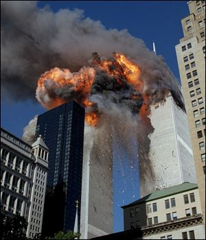 Smoke, flames and debris erupt from one of the World Trade Center towers after a plane strikes it Sept. 11, 2001. The first tower was already burning following a similar attack minutes earlier.