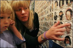 Jacob Campbell, 5, left, and his aunt Linda Maurer, both from the Queens borough of New York, look at the image of Campbell's mother and Maurer's sister Jill Marie Maurer-Campbell, who lost her life during the World Trade Center attacks, among other victims on America's 9-11 Victims' Memorial Quilt.