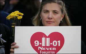 "A woman in an area for families of 9-11 victims  holds flowers and a sign that reads ""Never Forgotten"" at a memorial service marking the fifth anniversary of the attacks at the site of the former World Trade Center."