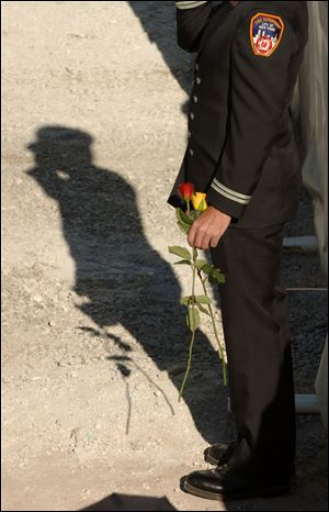 A New York Fire Department firefighter salutes during memorial ceremonies at the site of the former World Trade Center on Sept. 11, 2006.