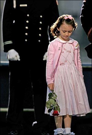 The daughter of a police office killed on 9-11 stands on stage during the reading of victims' names during ceremonies Sept. 11, 2006, at Ground Zero in New York.