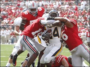 Toledo running back Adonis Thomas (24) runs the ball against Ohio State defenders Orhian Johnson (19) and Etienne Sabino (6)  during the fourth quarter.