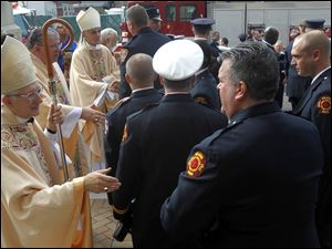 Most Rev. Leonard P. Blair, Bishop of Toledo, greets firefighters as they leave the church after the Firefighter Mass.