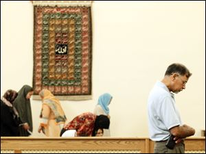 Dr. Fayyaz Hashmi, right, finishes his prayer in the mosque while the women leave their prayer area during