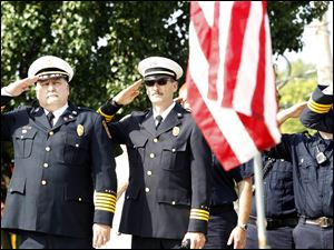 Sylvania Township/City of Sylvania Fire Chief Jeffrey Kowalski left, and Deputy Fire Chief Mike Froelich salute the flag during the ceremony.