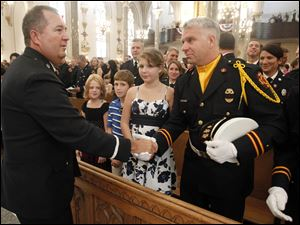Toledo Fire Lt. Robert Wiciak, left, offers his hand in peace during the Mass to Lt. Craig Ellis.