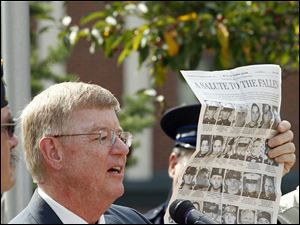 Mayor Craig Stough holds up a page of The Blade honoring  36 servicemen with have ties to northwest Ohio and southeast Michigan who have died.