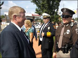 Mayor Craig Stough, left, speaks with Officer Kevin Steinman of the Sylvania Township Police Department, right, during the remembrance ceremony. Jeffrey Kowalski, fire chief of Sylvania Township/City of Sylvania, is next to Officer Steinman.