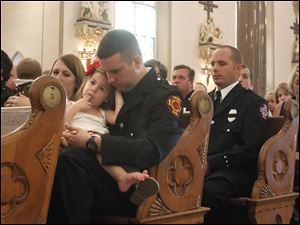 Toledo Fire and Rescue member Anthony Santiago holds his daughter Kathryn Santiago, while the names of the fallen are read.