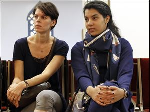 Regine Olsen, left, who is German but lives in Waterville, sits with Faiza Husain, right, and asks questions during the prayers in the mosque during