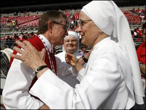 Sister Cecilia Sartorius of the Little Sisters of the Poor in Oregon hugs Ohio State President E. Gordon Gee before the game against Toledo as Sister Margaret Banar looks on.