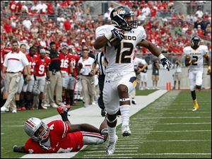 Toledo wide receiver Eric Page (12) scores his second touchdown of the first half against Ohio State free safety C.J. Barnett (4) during the first quarter.