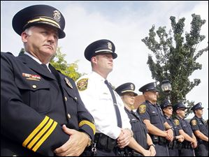 Sylvania Police Chief William Rhodus, left, stands with a line of police officers and fire fighters participating in a remembrance ceremony to mark the 10th anniversary of the terrorist attacks on Sept. 11, 2001 at River Centre Park in Sylvania.