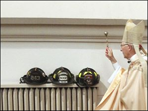 The Most Rev. Leonard P. Blair, bishop of Toledo, blesses helmets and artifacts from 9/11 during the Mass.