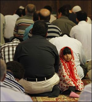 Yasser Ghafoor worships with his daughter, Ruba, 2, by his side at the Islamic Center of Greater Toledo in Perrysburg.