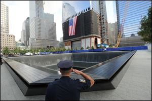 Danny Shea, a New York City Police Officer and military veteran, salutes at the north pool of the Sept 11. Memorial, during 10th anniversary ceremonies at the World Trade Center site.