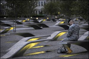 Maj. Tevye Yoblick spends a quiet moment at dawn at the Pentagon Memorial. The memorial includes an illuminated bench for each victim of the attack on the U.S. Defense Department's headquarters.
