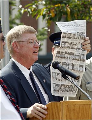 Mayor Craig Stough holds up a page of The Toledo Blade honoring  36 servicemen who have died that have ties to northwest Ohio and southeast Michigan during a remembrance ceremony to mark the 10th anniversary of the terrorist attacks on Sept. 11, 2001 at River Centre Park in Sylvania.
