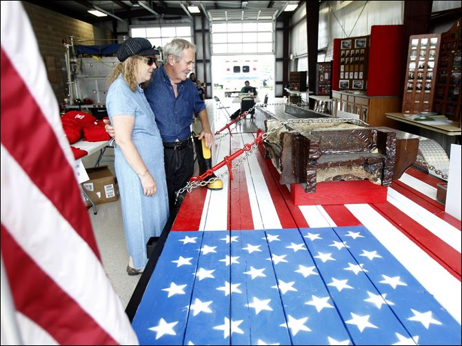 Janice Pennington Earl Ogren WTC beam Janice Pennington of Fulton County and Earl Ogren of Lambertville look over a steel beam from the World Trade Center that was on display at the Fulton County Fair. The beam eventually will be part of a permanent memorial at the fairgrounds.