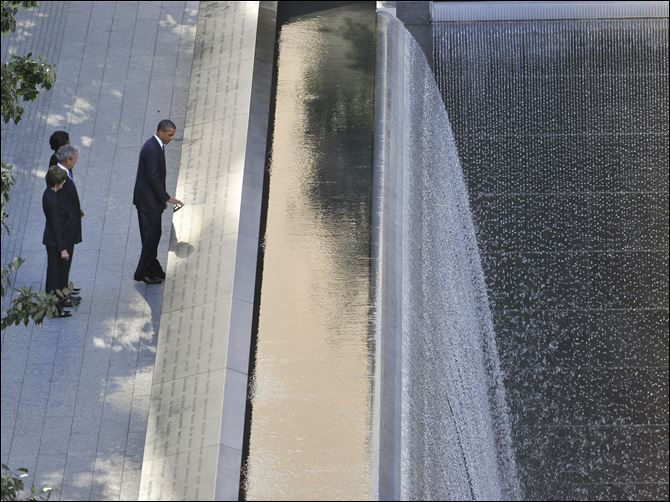 President Barack Obama, foreground, runs his hand along the names on the Sept. 11 memorial as former President George W. Bush, Laura Bush and Michelle Obama look on as they visit the memorial Sunday.
