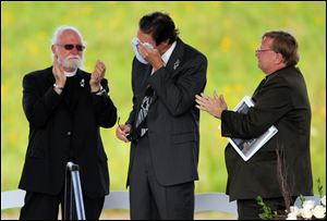 Wally Miller, Somerset County coroner, wipes his eyes as he is applauded during the service. Mr. Miller, who read a litany of remembrance, is flanked by the Rev. Paul Britton and the Rev. Robert Way.